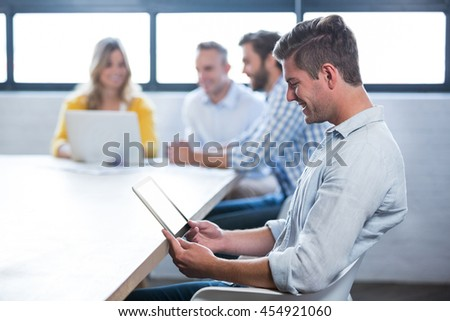 Side view of businessman using digital tablet while colleagues in background at office