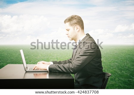 Side view of businessman using laptop on black desk outside on green grass. Sky background - stock photo