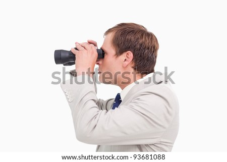 Side view of businessman using spy glasses against a white background - stock photo