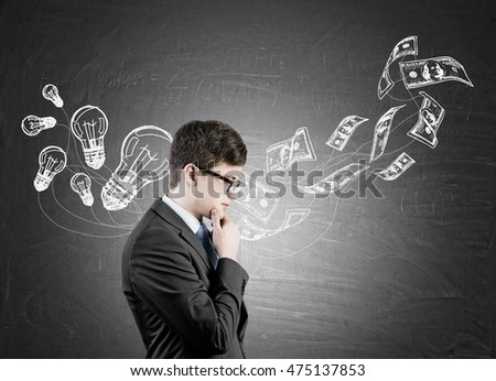 Side view of businessman wearing glasses standing near blackboard with light bulb and dollar notes sketches. Concept of business idea implementation.