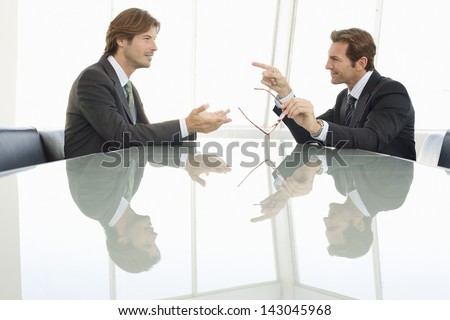 Side view of businessmen discussing in conference room - stock photo