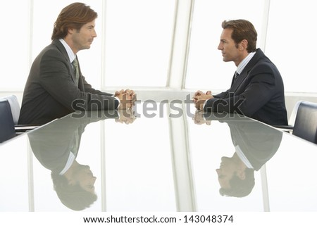 Side view of businessmen looking at each other in conference room - stock photo