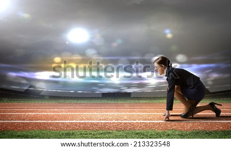 Side view of businesswoman at stadium standing in start position - stock photo
