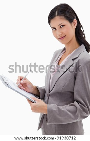 Side view of businesswoman taking notes against a white background