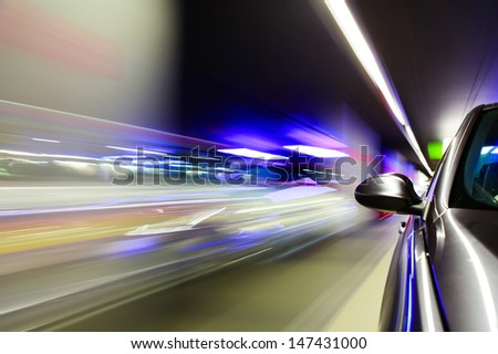 Side view of car driving in underground car park. - stock photo