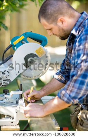 Side view of carpenter marking on wood with pencil at table saw - stock photo