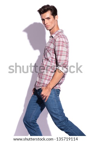 side view of casual young man stepping and looking at the camera with his thumbs in his pockets. isolated on white background - stock photo