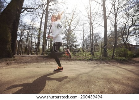Side view of caucasian female runner running outdoors in forest. Fitness woman athlete jogging in a park. Caucasian female model training outdoors. - stock photo