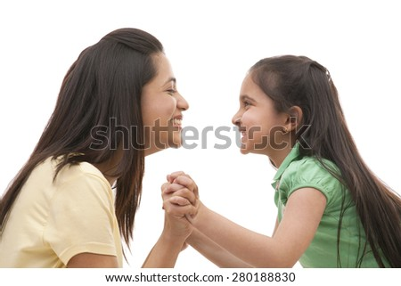 Side view of cheerful mother and daughter holding hands over white background - stock photo