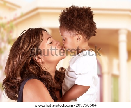 Side view of cheerful mother holding on hands cute little curly son and kiss him, spending time outdoors near great beautiful house, happy African family - stock photo