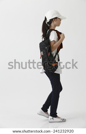 side view of chinese girl with cap walking - stock photo