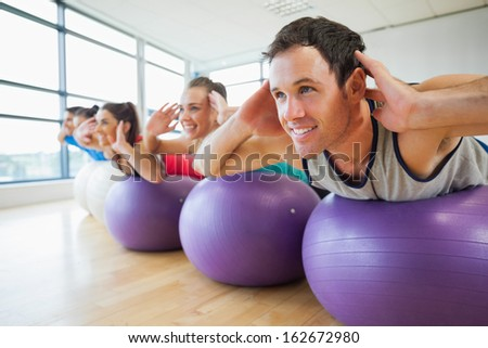 Side view of class exercising on fitness balls in a row at the bright gym - stock photo