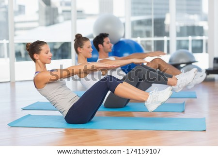 Side view of class stretching on mats at yoga class in fitness studio