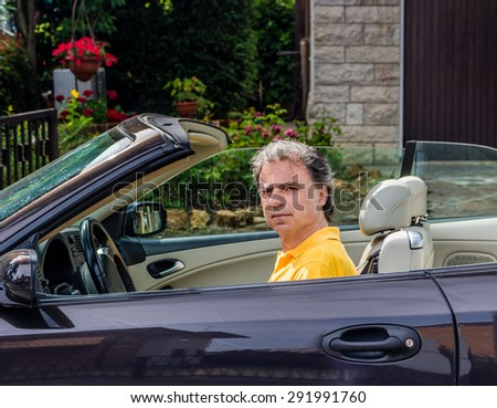 Side view of classy senior sportsman with three-day beard and salt and pepper hair wearing a yellow polo shirt while he is driving a dark brown car in residential neighborhood