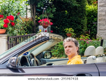 Side view of classy senior sportsman with three-day beard and salt cand pepper hair wearing a yellow polo shirt while he is driving a dark brown car in residential neighborhood