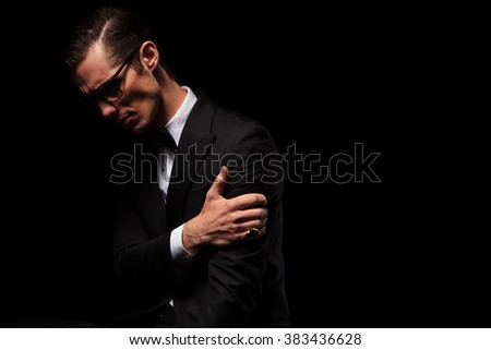 side view of classy smart man in black suit posing looking down while touching his arm in dark studio background - stock photo