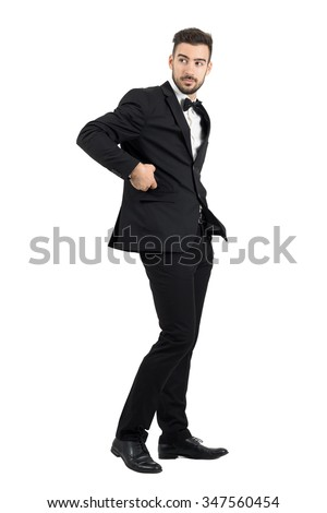 Side view of confident handsome man in tuxedo putting cellphone in coat pocket turning behind.  Full body length portrait isolated over white studio background.  - stock photo