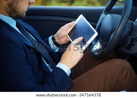 Side view of confident senior man in formalwear sitting in car and hold tablet pc - stock photo