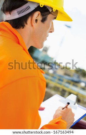 Side view of construction worker writing on clipboard at construction site - stock photo