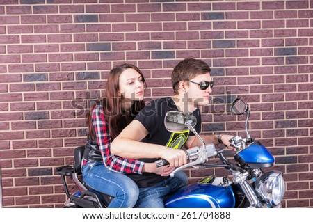 Side View of Cool Young Couple Riding on Classic Blue Motorcycle in front of Brick Wall - stock photo