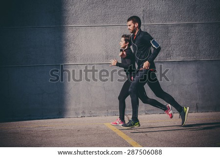 Side view of couple running in an urban environment - stock photo