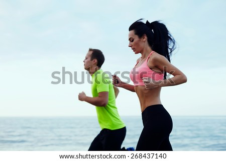 Side view of couple running outdoors, fit athlete man and fitness woman working out together running on beautiful beach with sea horizon on background - stock photo