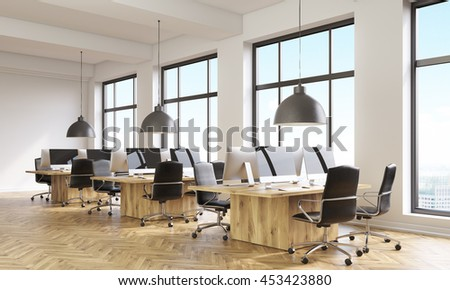 Side view of coworking office interior with computer monitors on wooden desks, parquet flooring, concrete walls and panoramic windows with city view. 3D Rendering