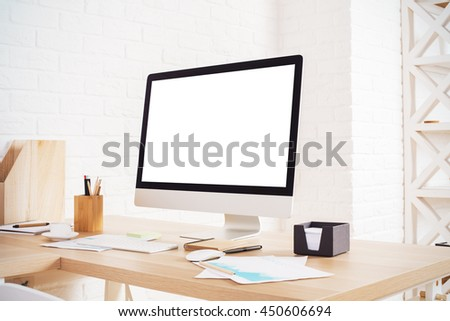 Side view of creative designer workplace with blank white computer monitor, various stationery and decorative items on brick wall background. Mock up - stock photo