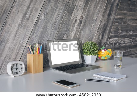 side view of creative designer workspace with white laptop smartphone stationery items clock