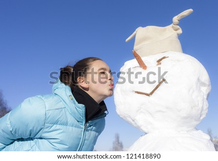Side view of cute girl kissing snowman outdoor, on a sunny winter day