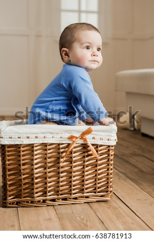 Side view of cute little baby boy sitting inside of braided box at home
