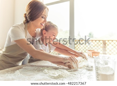 Side view of cute little girl and her beautiful mom in aprons smiling while flattening the dough using a rolling pin in the kitchen