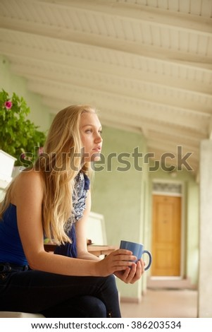 Side view of daydreaming young blonde woman drinking tea in balcony. - stock photo