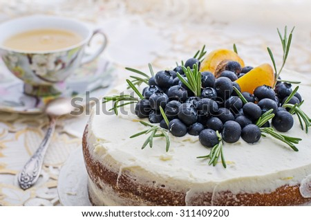 side view of delicious home made layered cake with cream, berries, rosemary and nectarine on top on a decorative white table cloth next to a vintage cup of tea - stock photo