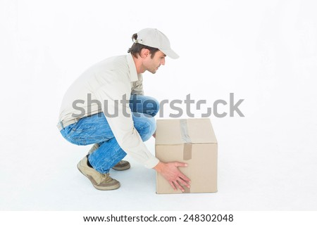Side view of delivery man crouching while picking cardboard box against white background - stock photo