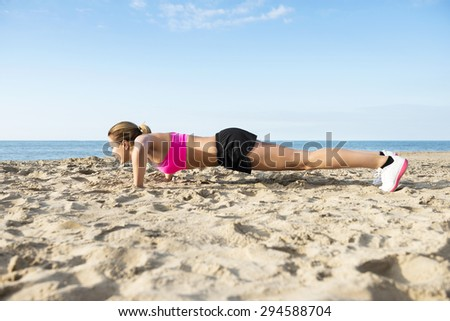 Side view of determined young woman doing push-ups on beach - stock photo