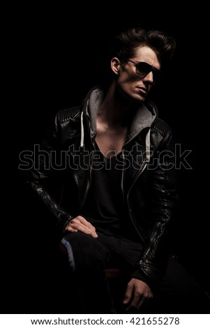 side view of dramatic young man in leather jacket posing in studio