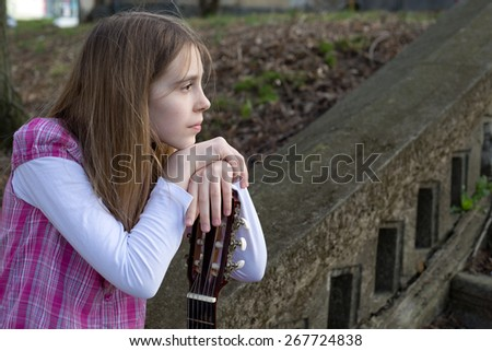 Side View of Dreamy Young Girl Leaning on Her Guitar - stock photo