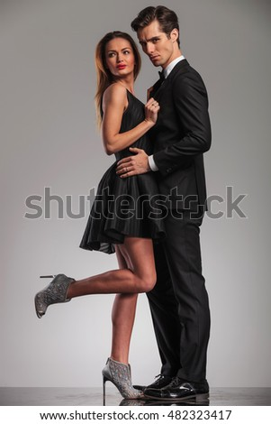 side view of embraced elegant couple in black clothes, woman looking back while holding her lover