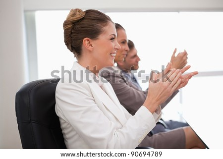Side view of employees giving applause after presentation