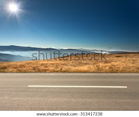 Side view of empty asphalt road and cloudy mountains in ...