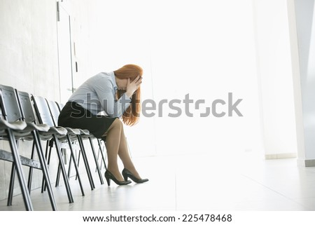 Side view of exhausted businesswoman sitting on chair in office - stock photo