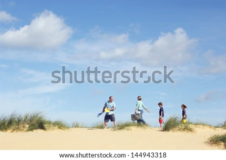 Side view of family walking sand dune on beach against the sky - stock photo