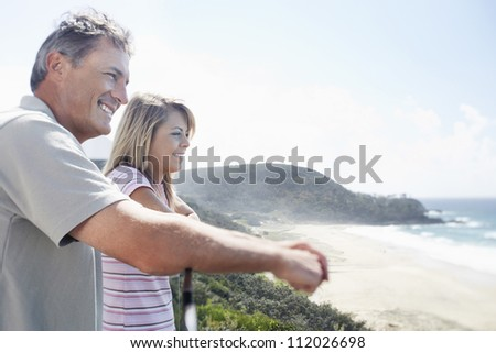 Side view of father and daughter looking out at ocean from balcony