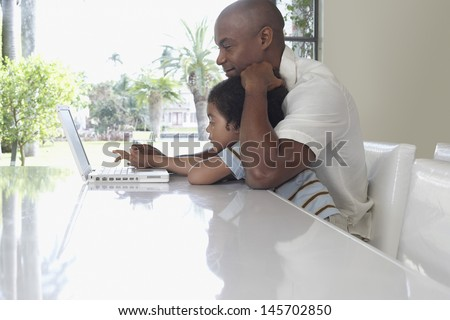 Side view of father and son using laptop at dining table - stock photo
