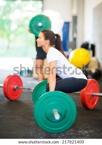 Side view of female athlete lifting barbell at healthclub - stock photo