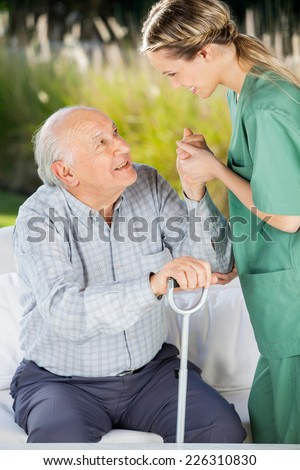 Side view of female caretaker helping senior man to get up from couch - stock photo