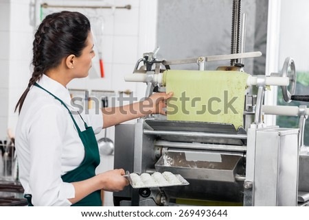 Side view of female chef processing ravioli pasta in machinery at commercial kitchen