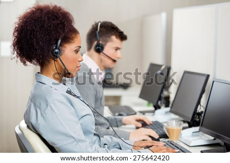Side view of female customer service representatives with colleague working in call center - stock photo