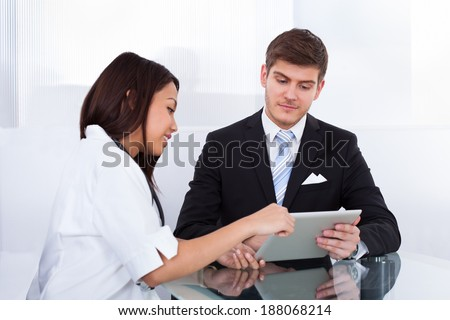 Side view of female doctor showing digital tablet to businessman in clinic - stock photo